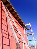 Alte Strichleitern und Gebäude Stockbilder