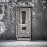 Alte Tür in der dunklen Betonmauer mit Ausrufszeichen Stockbild