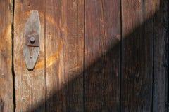 Alte Tür mit hölzernen Planken im Licht und im Schatten lizenzfreie stockbilder