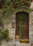 Alte Tür mit Rosen in Montechiaro-d'Acqui Lizenzfreie Stockbilder