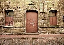 Alte Tür und 2 Fenster in der Backsteinmauer Stockfotos