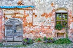Alte Tür und neues Fenster in einer alten Backsteinmauer Stockbilder