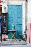 Alte Türkismetalltür mit Tabelle und Stuhl als schöner Weinlesehintergrund Stockfotos