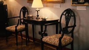 Alte Tabelle und zwei Stühle mit einer Lampe stock footage