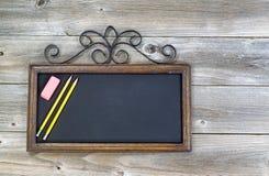 Alte Tafel mit Bleistiften und Radiergummi auf Holz Lizenzfreies Stockbild