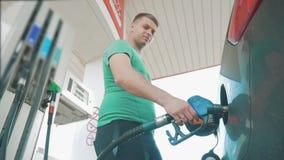 Alte Tankstelle der Mann gießt Benzin im Auto Benzintreibstoff wird in den Autoschwarzauto-Schlauchlebensstil gegossen stock footage