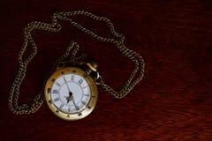 Alte Taschenuhr auf einem Holztisch Stockbild