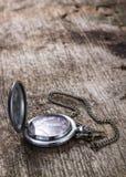 Alte Taschenuhr auf hölzernem Hintergrund Stockfotos
