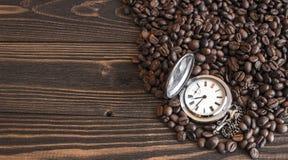 Alte Taschenuhr, die auf den Kaffeebohnen liegt Lizenzfreies Stockbild