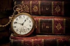 Alte Taschenuhr und -bücher im zurückhaltenden Exemplarplatz Lizenzfreies Stockfoto