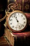 Alte Taschenuhr und -bücher in zurückhaltendem Stockbilder
