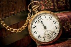 Alte Taschenuhr und -bücher in zurückhaltendem Lizenzfreies Stockfoto