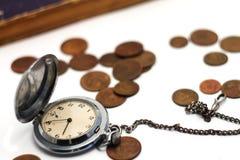 Alte Taschenuhrnahaufnahme auf einem Hintergrund von unscharfen Münzen Stockfotografie