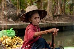 Alte thailändische Frau, die Frucht an sich hin- und herbewegendem Markt, Damnoen Saduak, Thailand verkauft Lizenzfreie Stockbilder
