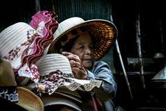 Alte thailändische Frau, die Hüte an sich hin- und herbewegendem Markt Damnoen Saduak verkauft Stockbild