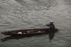 Alte thailändische Frau schaufelt hölzernes Boot im Fischereihafen Stockfotografie