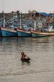 Alte thailändische Frau schaufelt hölzernes Boot im Fischereihafen Lizenzfreies Stockbild