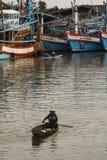 Alte thailändische Frau schaufelt hölzernes Boot im Fischereihafen Stockfotos
