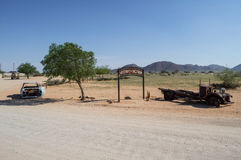 Alte Timer-Auto-Wracke vor einer Wüsten-Landschaft in Namibia Lizenzfreies Stockfoto
