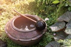 Alte Tonwaren mit Wasser im Garten stockbild