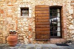 Alte toskanische Wand - Brown-Tür in einem mittelalterlichen Stein und in einer Backsteinmauer Stockfotos