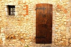 Alte toskanische Wand - Brown-Tür in einem mittelalterlichen Stein und in einer Backsteinmauer Lizenzfreies Stockbild