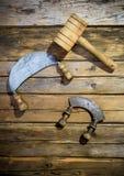 Alte traditionelle Messer und hölzerner Hammer, die an der Wand hängt Lizenzfreie Stockbilder