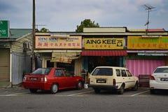 Alte traditionelle Shophäuser an einer Kleinstadt in Malaysia mit Autos parkten in der Front Stockfoto