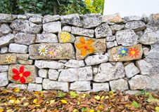 Alte traditionelle Steinwand mit gemalten Blumen in Puglia, Italien Stockbild