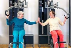 Alte trainierende Damen beim Berühren ihrer Palmen Lizenzfreies Stockfoto