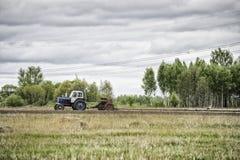 Alte Traktoren, die auf dem Gebiet arbeiten Lizenzfreie Stockbilder