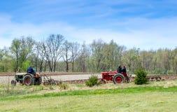 Alte Traktoren, die ein Feld pflügen Lizenzfreie Stockfotos