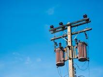 Alte Transformatoren auf konkretem Pfosten mit blauem Himmel Lizenzfreies Stockbild