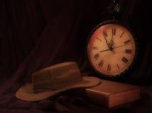 Alte Uhr, altes Buch und Hut Stockfoto