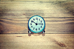 Alte Uhr auf dem hölzernen Hintergrund Stockbild