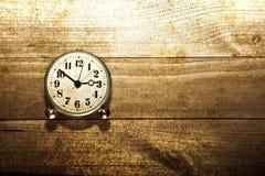 Alte Uhr auf dem hölzernen Hintergrund Lizenzfreies Stockfoto