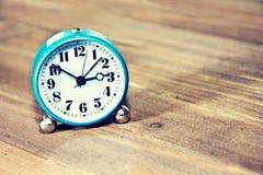 Alte Uhr auf dem hölzernen Hintergrund Stockfotos