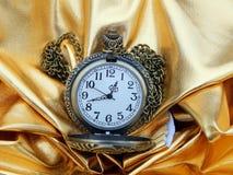 Alte Uhr auf einem Goldsatinhintergrund Lizenzfreie Stockfotografie