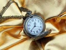 Alte Uhr auf einem Goldsatinhintergrund Stockbilder