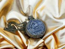 Alte Uhr auf einem Goldsatinhintergrund Stockfotos
