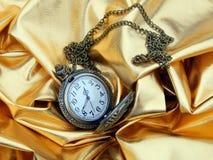Alte Uhr auf einem Goldsatinhintergrund Lizenzfreies Stockfoto