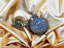 Alte Uhr auf einem Goldsatinhintergrund Lizenzfreies Stockbild