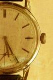 Alte Uhr auf einem Goldschmutzhintergrund Lizenzfreie Stockbilder