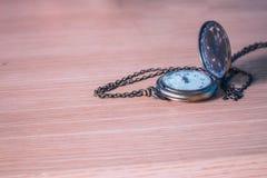 Alte Uhr auf einem hölzernen Stockbild