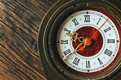 Alte Uhr auf einem hölzernen Hintergrund Stockbild