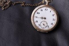 Alte Uhr auf einem Hintergrund des schwarzen Leders Lizenzfreies Stockfoto