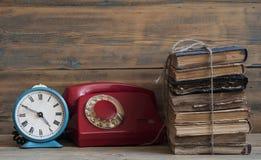 Alte Uhr auf einer alten hölzernen Tabelle mit einem Stapel Büchern Lizenzfreies Stockbild