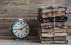 Alte Uhr auf einer alten hölzernen Tabelle mit einem Stapel Büchern Lizenzfreie Stockbilder
