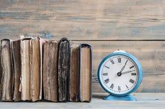 Alte Uhr auf einer alten hölzernen Tabelle mit einem Stapel Büchern Stockfoto