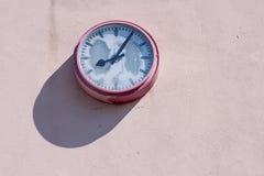 Alte Uhr auf einer Hausmauer Lizenzfreie Stockbilder